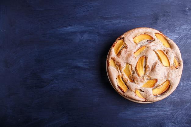 Sweet persimmon pie on black wooden.