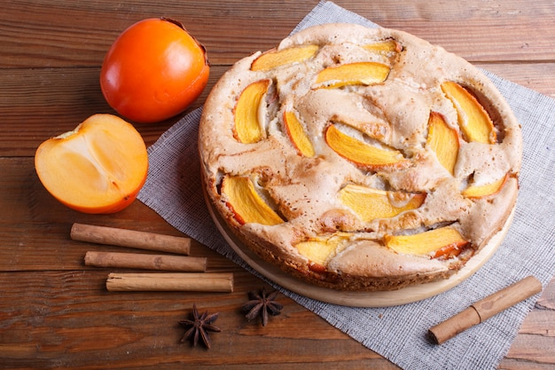 Sweet persimmon pie on brown wooden.