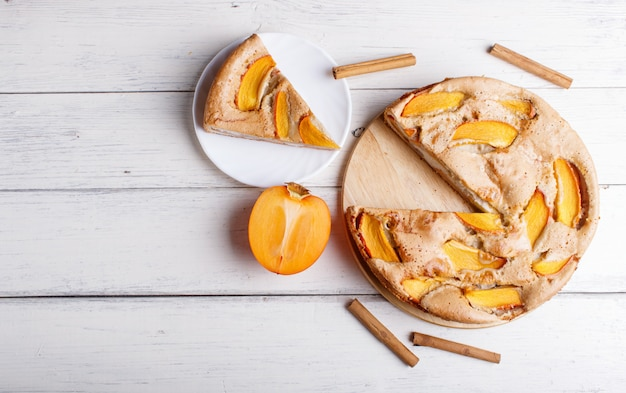 Sweet persimmon pie on white wooden surface.