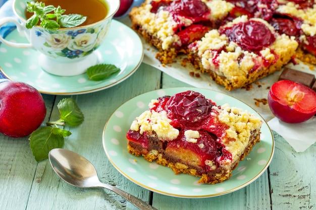 초콜릿과 신선한 자두를 곁들인 달콤한 파이 타르트 식탁에 자두를 곁들인 맛있는 케이크