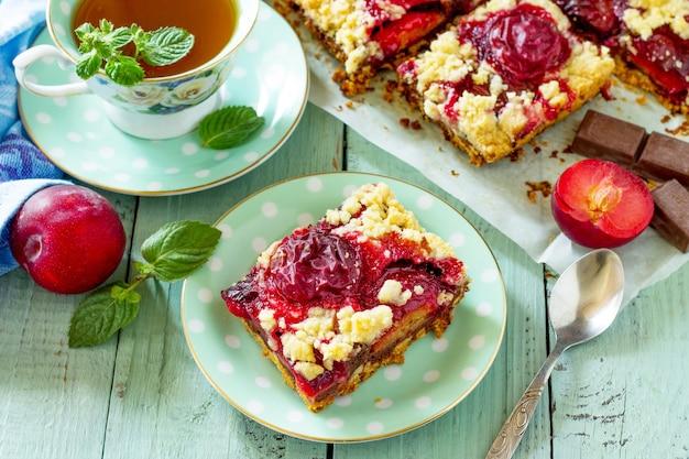 신선한 자두를 곁들인 달콤한 파이 타르트 식탁에 자두를 곁들인 맛있는 케이크