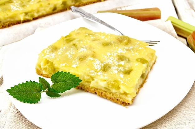 나무 판자를 배경으로 키친 타월에 민트를 얹은 접시에 바닐라 푸딩, 루바브, 크림으로 속을 채운 달콤한 파이