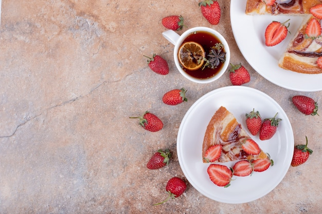 Sweet pie with strawberry in a white plate with a cup of tea