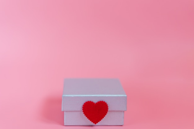 Sweet pink background with a silver gift box and decoration seal with a craft little red heart symbol of love and care