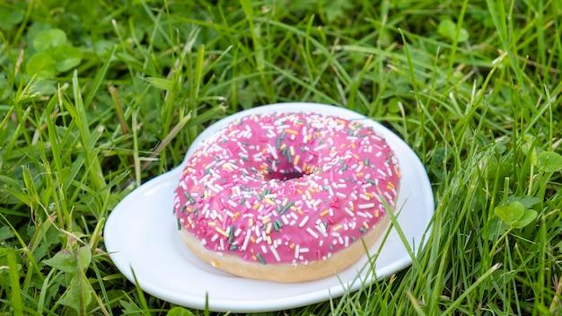 緑の芝生の上のプレートに甘いピンクのドーナツ。