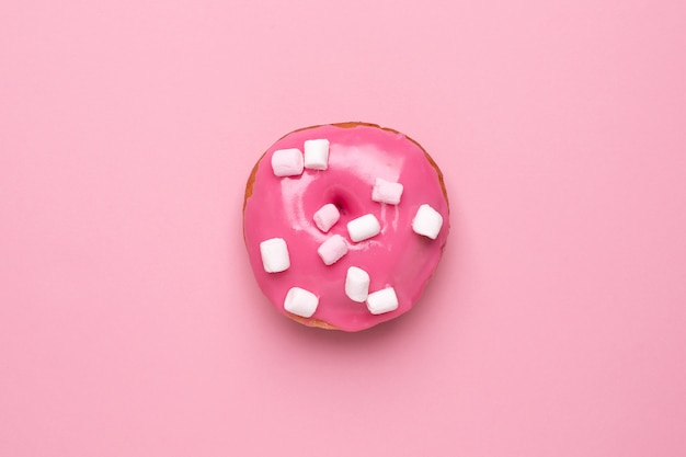 Sweet pink donut with marshmallows on a pink background flat lay