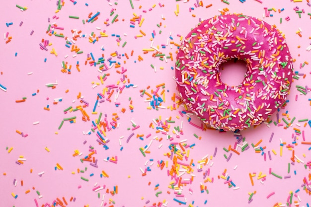 Sweet pink donut with multicolored sprinkles on a pink surface flat lay