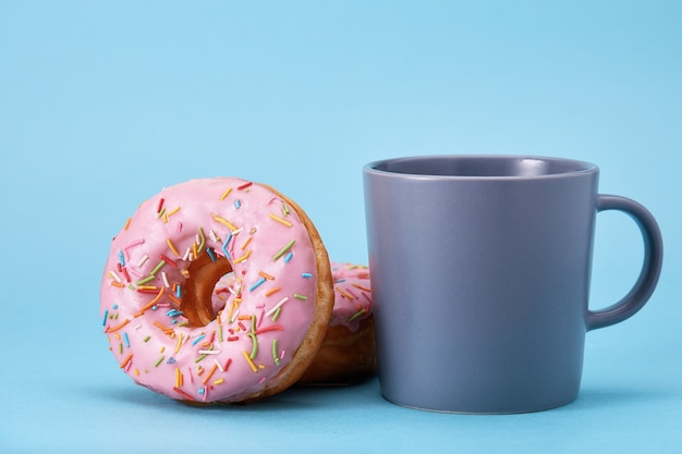 Sweet pink donuts with a blue mug on a blue background. concept dessert, sweet life, we are what we eat. blue background, copy space.