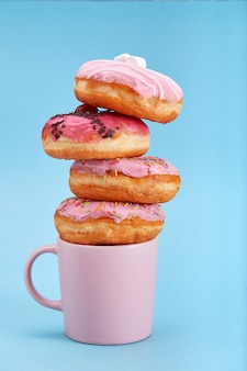 Sweet pink donuts with a pink mug on a blue background. concept dessert, sweet life, we are what we eat. blue background, copy space.
