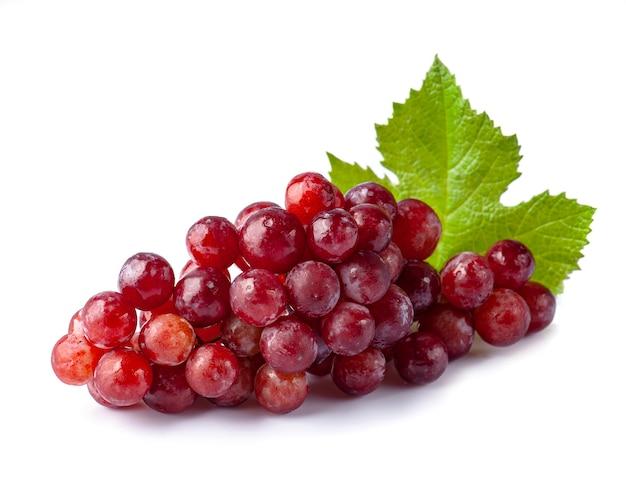 Сладкий розовый виноград с листьями на белом фоне.