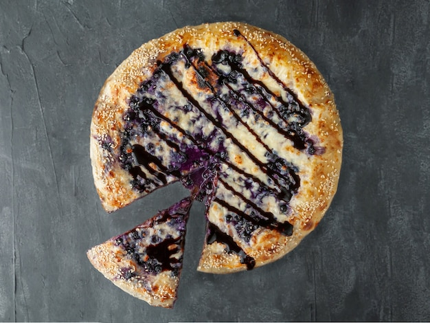 Sweet pizza. blueberries, cream cheese, mozzarella and sulguni, poured with chocolate topping. a piece is cut off from pizza. view from above. on a gray concrete background. isolated.