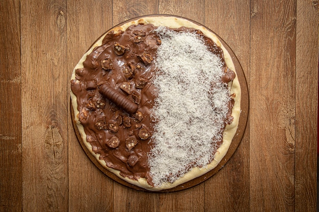 Sweet pizza with chocolate and grated coconut. top view.