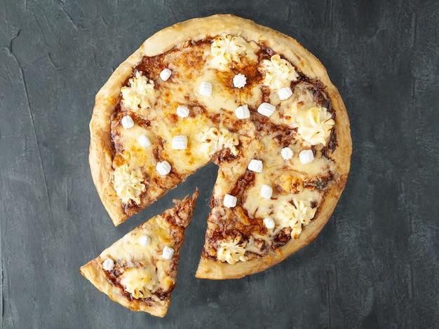 チョコレートペーストの甘いピザヌテッラ、バナナ、クリームチーズ、モッツァレラチーズ、スルグニ、マシュマロ。 。ピザから一片が切り取られます。上からの眺め。灰色のコンクリートの背景に。孤立。