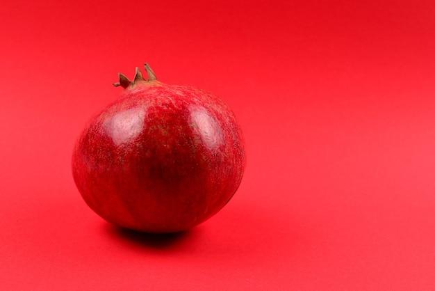 赤い背景の上の甘いザクロ