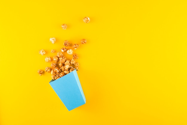Sweet popcorn in a blue box on a yellow table.