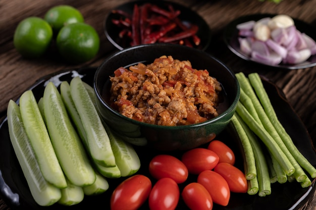 Сладкая свинина в черной миске с огурцами, длинной фасолью, помидорами и гарнирами