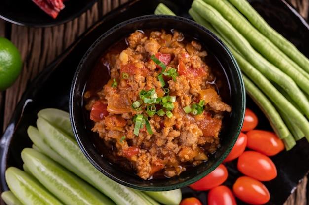 きゅうり、長豆、トマト、おかずが入った黒いボウルの甘い豚肉