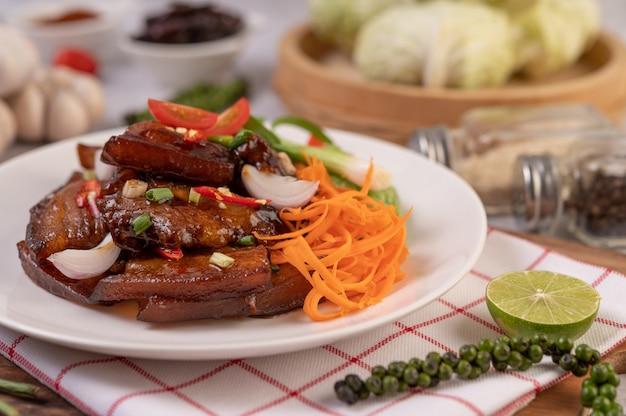 Сладкая свинина в белой тарелке с нарезанным зеленым луком, чили, лаймом, тыквой, помидорами и чесноком.