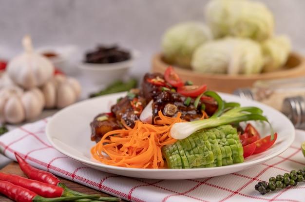 다진 파, 칠리, 라임, 조롱박, 토마토 및 마늘을 곁들인 흰 접시에 달콤한 돼지 고기.