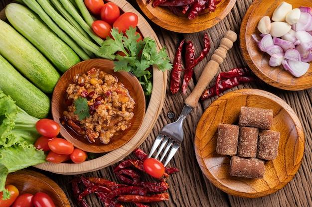 Сладкая свинина в деревянной миске с огурцом, длинной фасолью, помидорами и гарнирами.