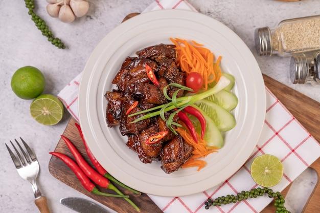 ネギのみじん切り、唐辛子、ライム、キュウリ、トマト、ニンニクの白い皿に甘い豚肉。