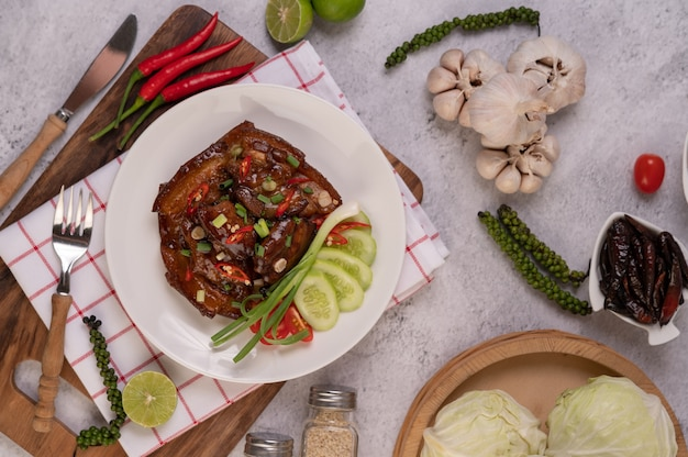 Sweet pork on a white plate with chopped scallions, chili, lime, cucumber, tomato, and garlic.