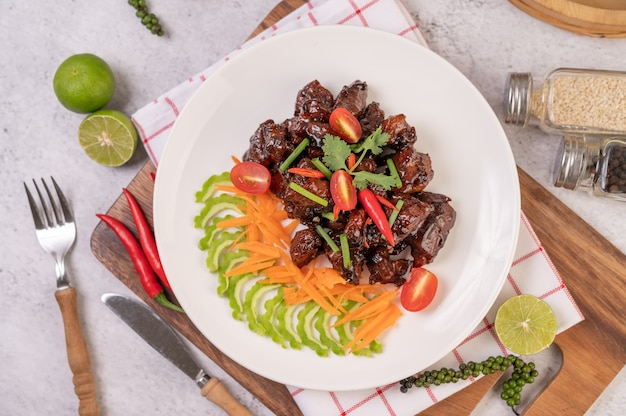 Sweet pork in a white plate with chopped scallions, chili, lime, gourd, tomato and garlic.