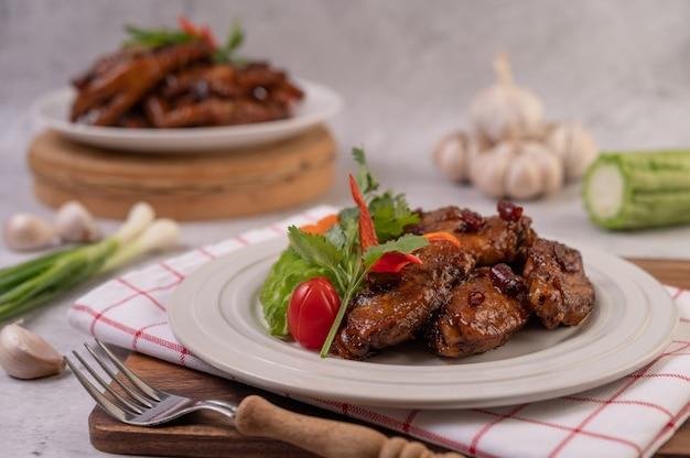 Maiale dolce in un piatto bianco con scalogno tritato, peperoncino, lime, zucca, pomodoro e aglio.