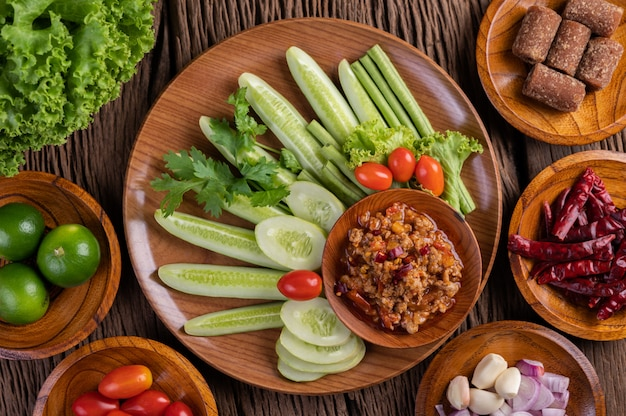 Sweet pork in a wooden bowl with cucumber, long beans, tomatoes, and side dishes.