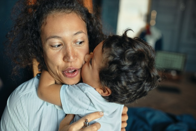 Sweet portrait of cute tender mixed race little boy kissing young his excited mom on cheek, keeping arms around her neck.
