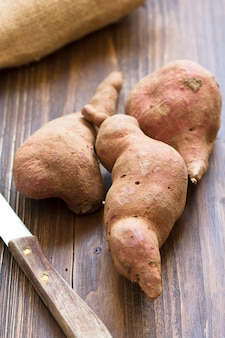 Sweet potato on brown wooden surface