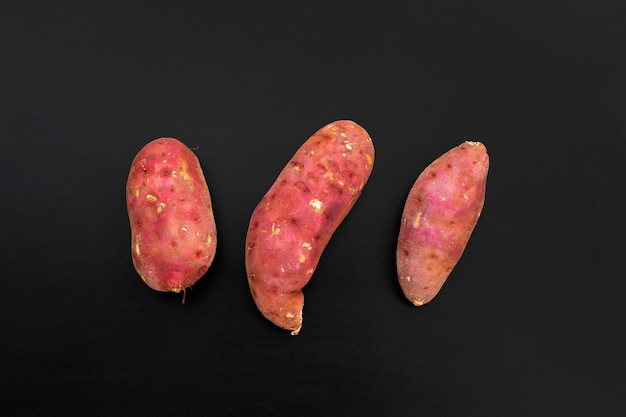 Sweet potato on dark background. top view