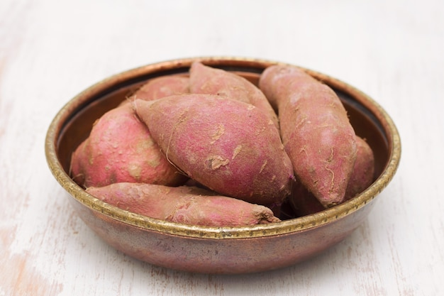 Sweet potato in dish on wooden background