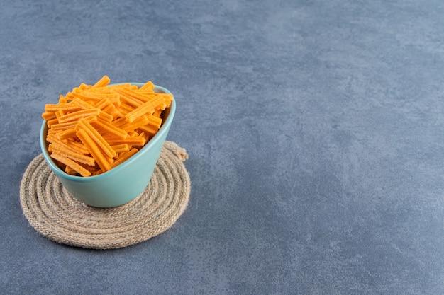 Сладкий картофель фри в миске на подставке, на мраморном фоне.