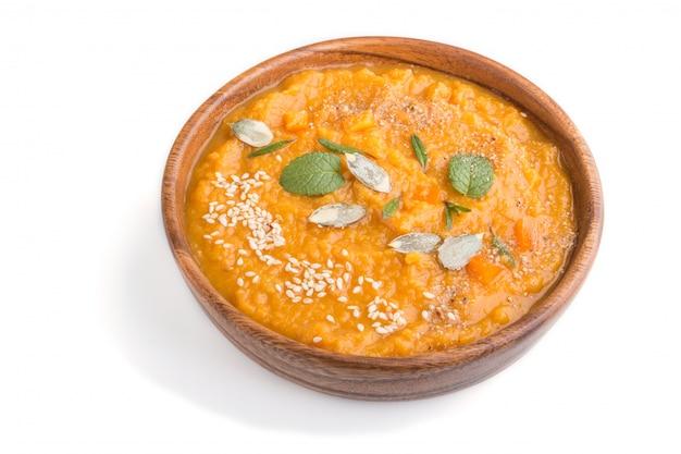 Сладкий картофель или батата крем суп с кунжутом в деревянной миске, изолированные на белой поверхности. вид сбоку.