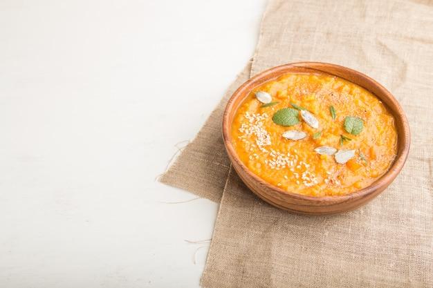 Сладкий картофель или батата крем-суп с кунжутом в деревянной миске на белом фоне деревянные. вид сбоку, копия пространства.