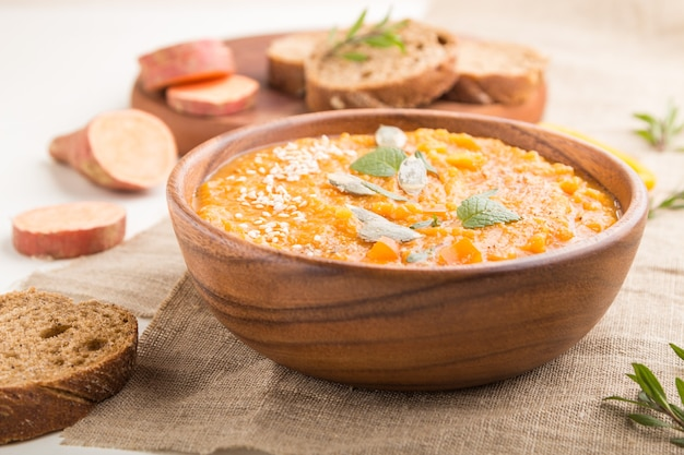 Суп-пюре из сладкого картофеля или батата с семенами кунжута в деревянной миске на белой деревянной поверхности с льняной тканью