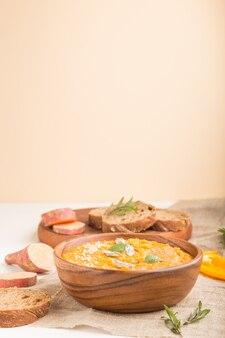 Сладкий картофель или батата крем-суп с кунжутом в деревянной миске на белой деревянной стене. вид сбоку, выборочный фокус.