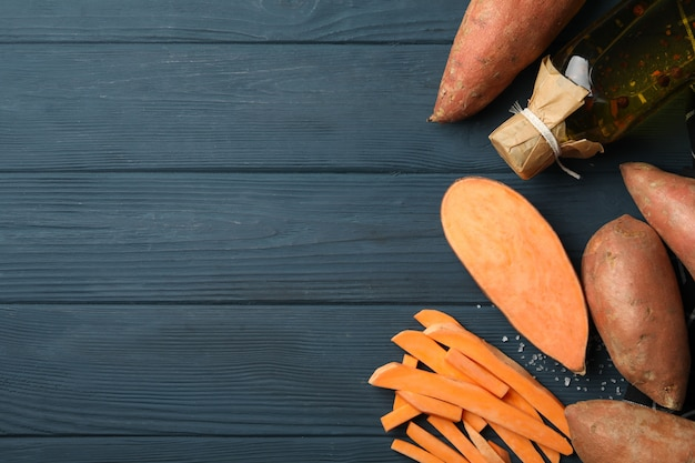 Sweet potatoes and ingredients on wooden surface