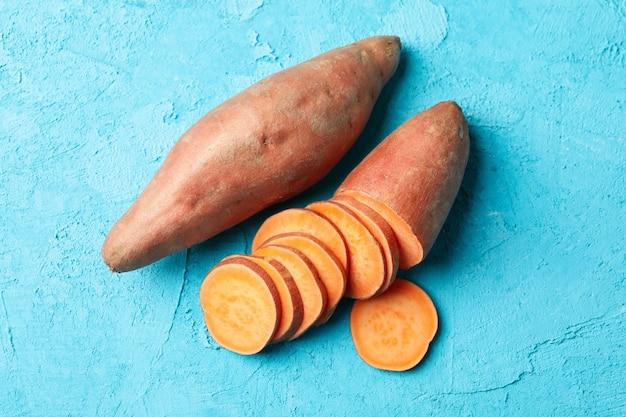 Сладкий картофель на синей поверхности. овощи