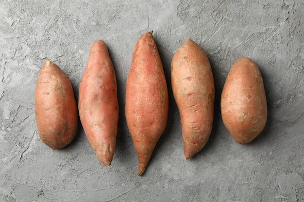 Сладкий картофель на серой поверхности. овощи