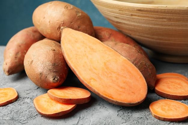 Сладкий картофель на сером столе. овощи