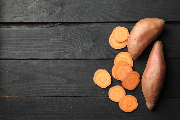 Sweet potatoes on wooden surface. vegetables
