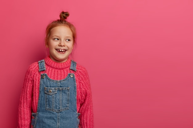Sweet pretty girl smiles positively and looks aside, has ginger hair knot, toothy smile, wears knitted sweater and dungarees, enjoys school free days and weekends, laughs at something funny.