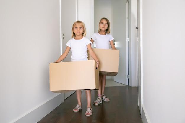 廊下でカートンボックスを運んで、新しいアパートに移動する甘いかわいい女の子