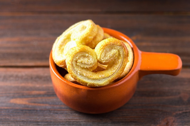Sweet pretzels made of puff pastry in a bowl on a wooden table