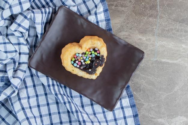 어두운 접시에 화려한 사탕과 달콤한 퍼프 케이크