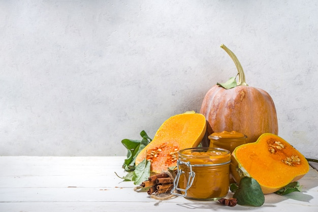 Sweet pumpkin pie jam. homemade confiture with pumpkin puree and traditional autumn spices. cinnamon, anise. with fresh butternut squash and fall leaves on white wooden background