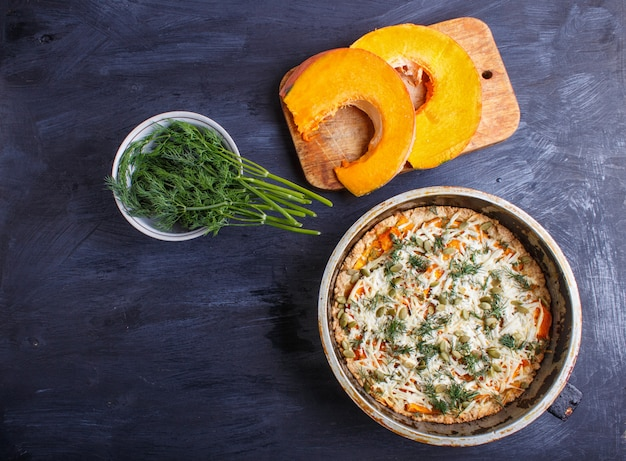 Sweet pumpkin pie with cheese and dill on black wooden background.