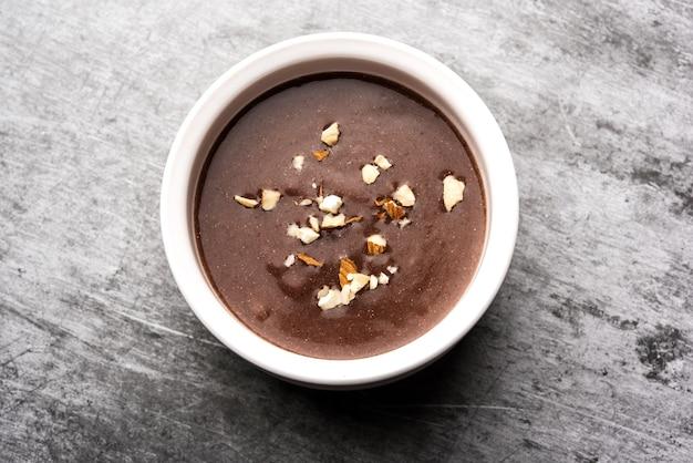 Sweet ragi malt or healthy ragi porridge in a bowl garnished with crushed dry fruits